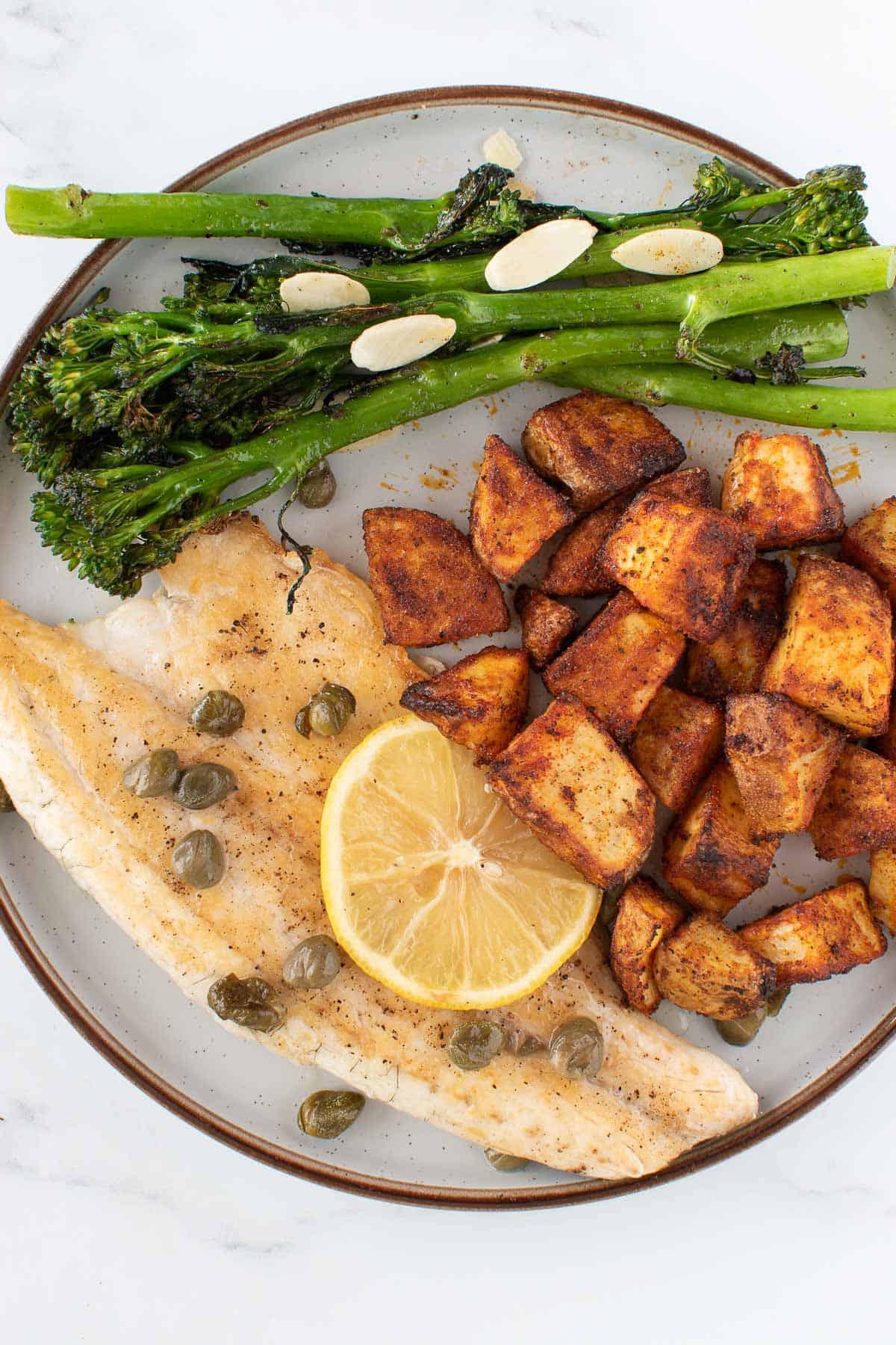 Sea bass, potatoes and broccoli on a plate.