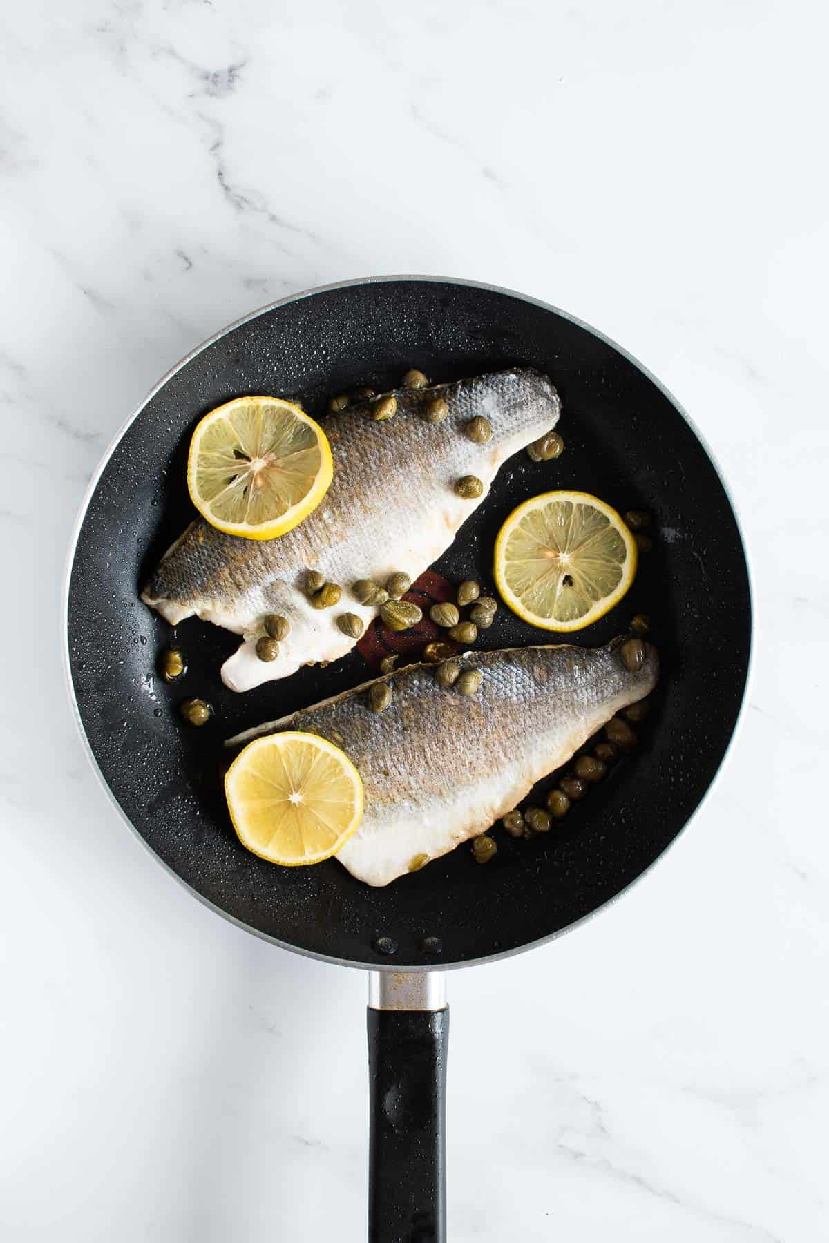 A frying pan with sea bass fillets, lemon and capers.