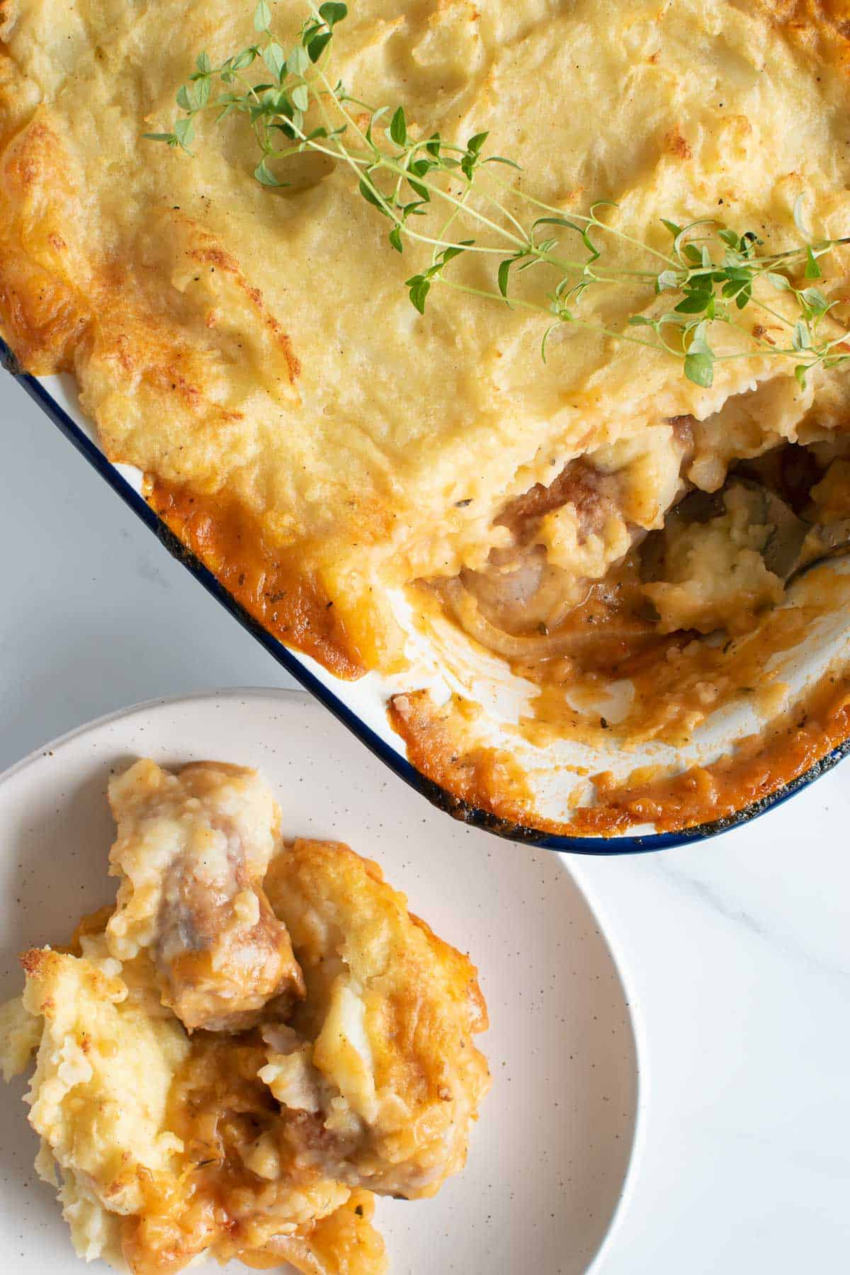 A pie dish filled with sausage and mashed potato pie, with a serving plated up on the side.