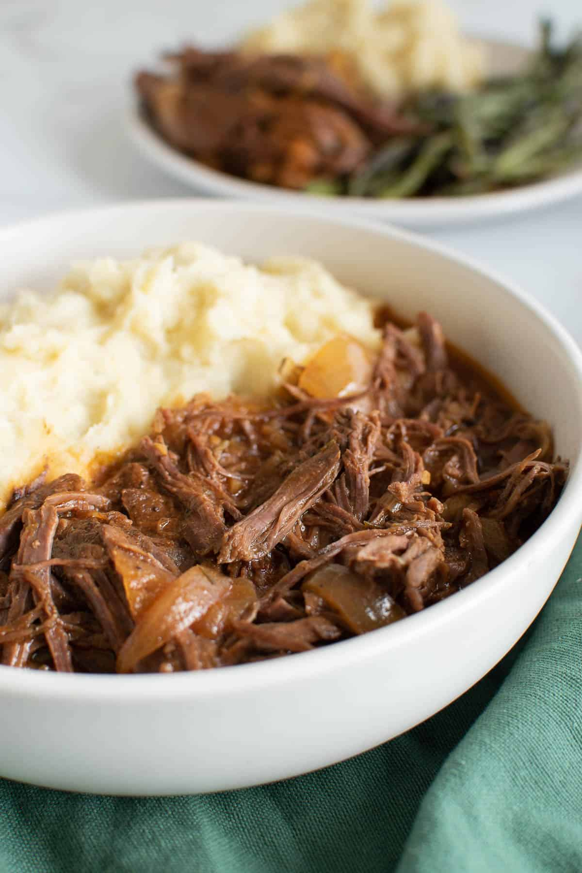 Close up of shredded beef and mashed potatoes.