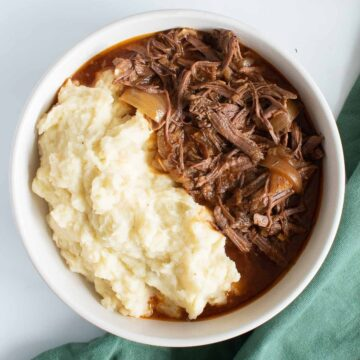 A bowl of shredded braising steak and mashed potatoes.