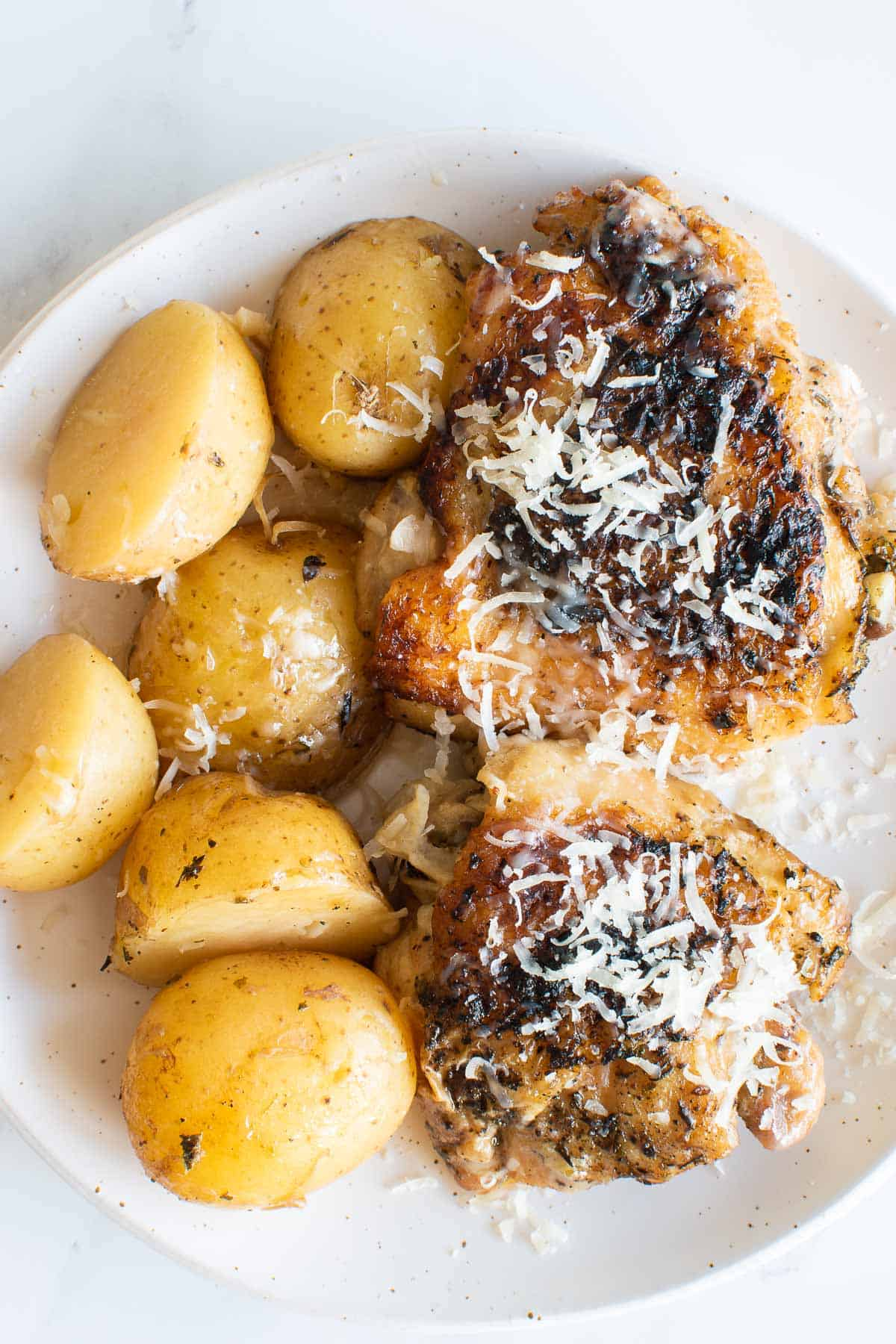 A plate of garlic Parmesan chicken and potatoes.