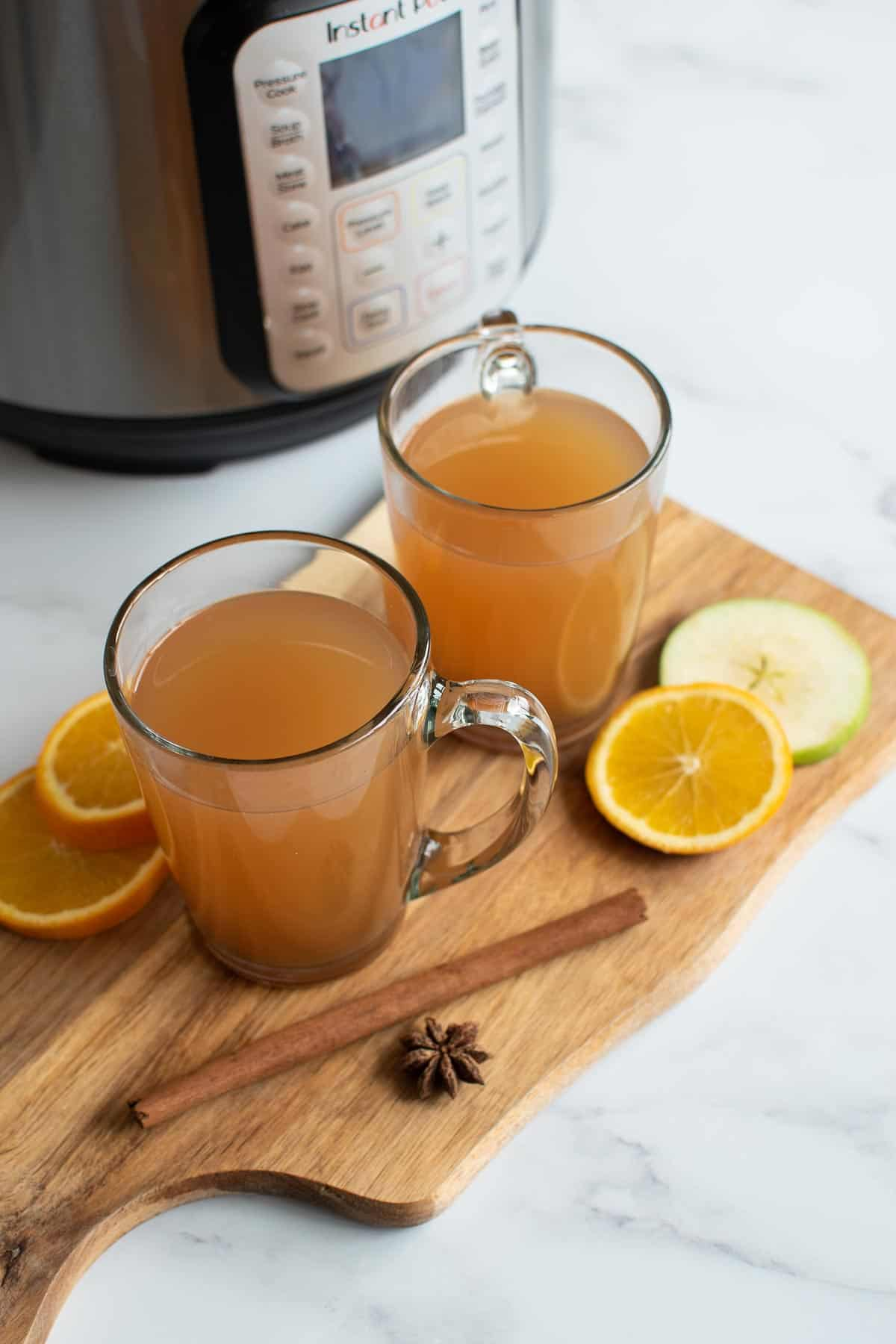 Two glasses of hot mulled cider with cinnamon, star anise and oranges.