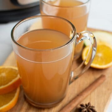 Glasses filled with hot cider, with cinnamon sticks and orange slices on the side.
