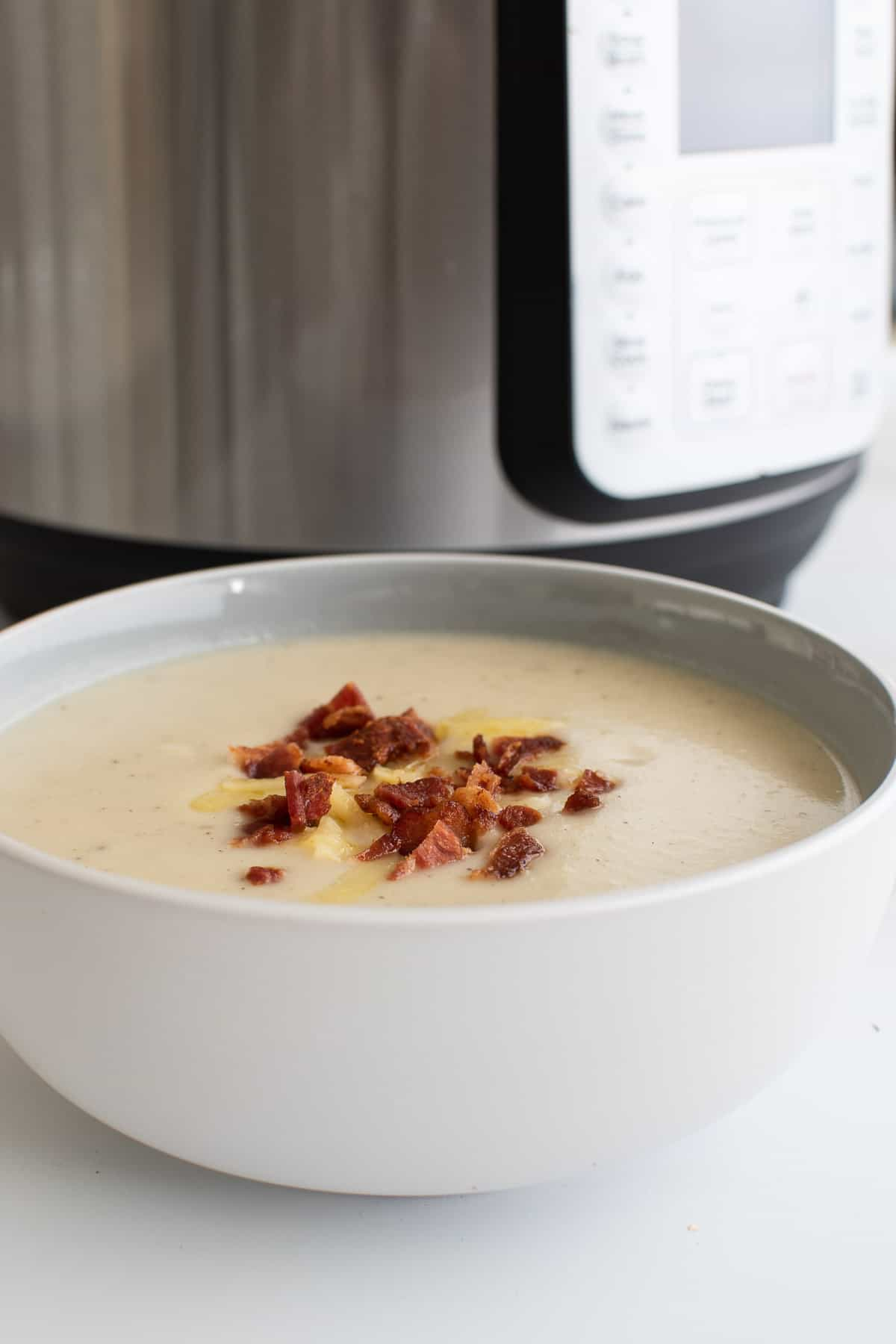 A bowl of cauliflower soup in front of an Instant Pot.