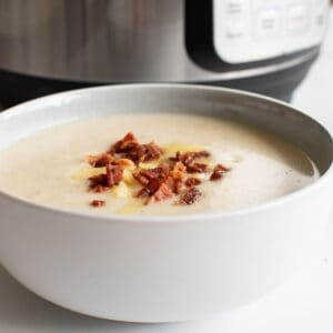 Instant Pot cauliflower soup topped with bacon in a bowl.