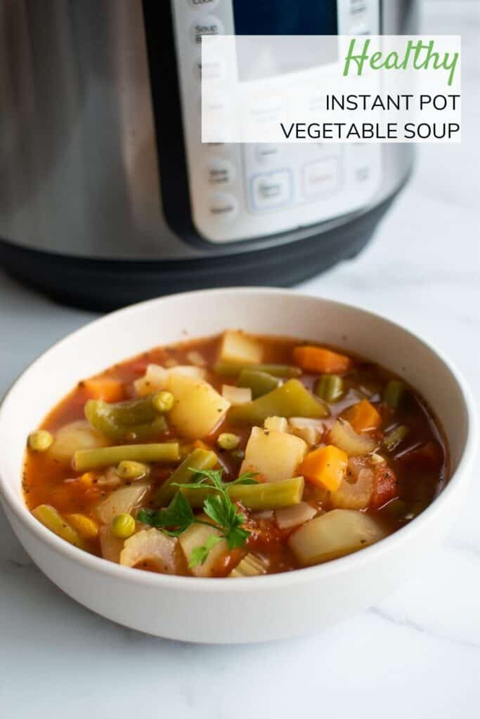A bowl of vegetable soup in front of an Instant Pot.