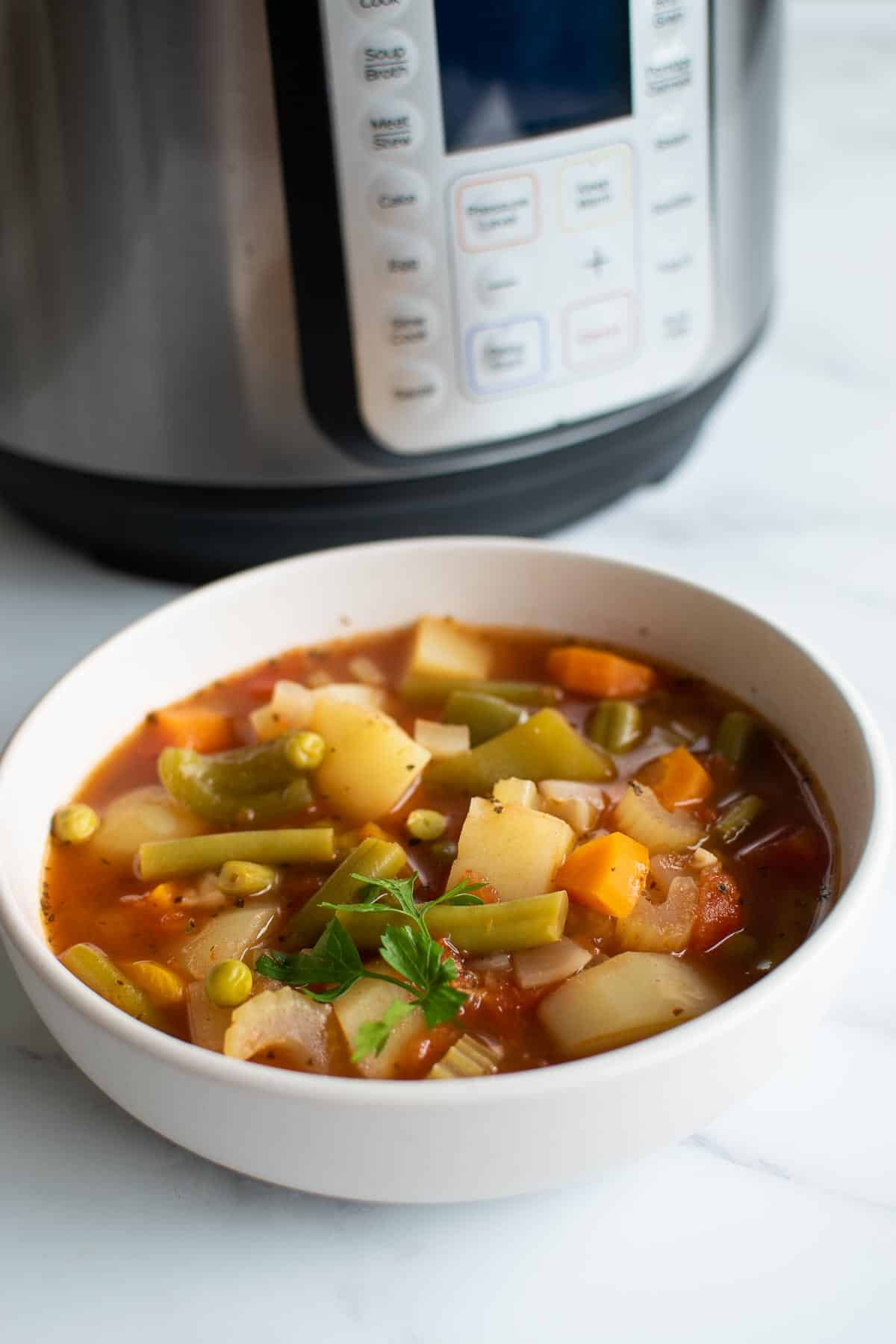 A bowl of vegetable soup in front of Instant Pot.