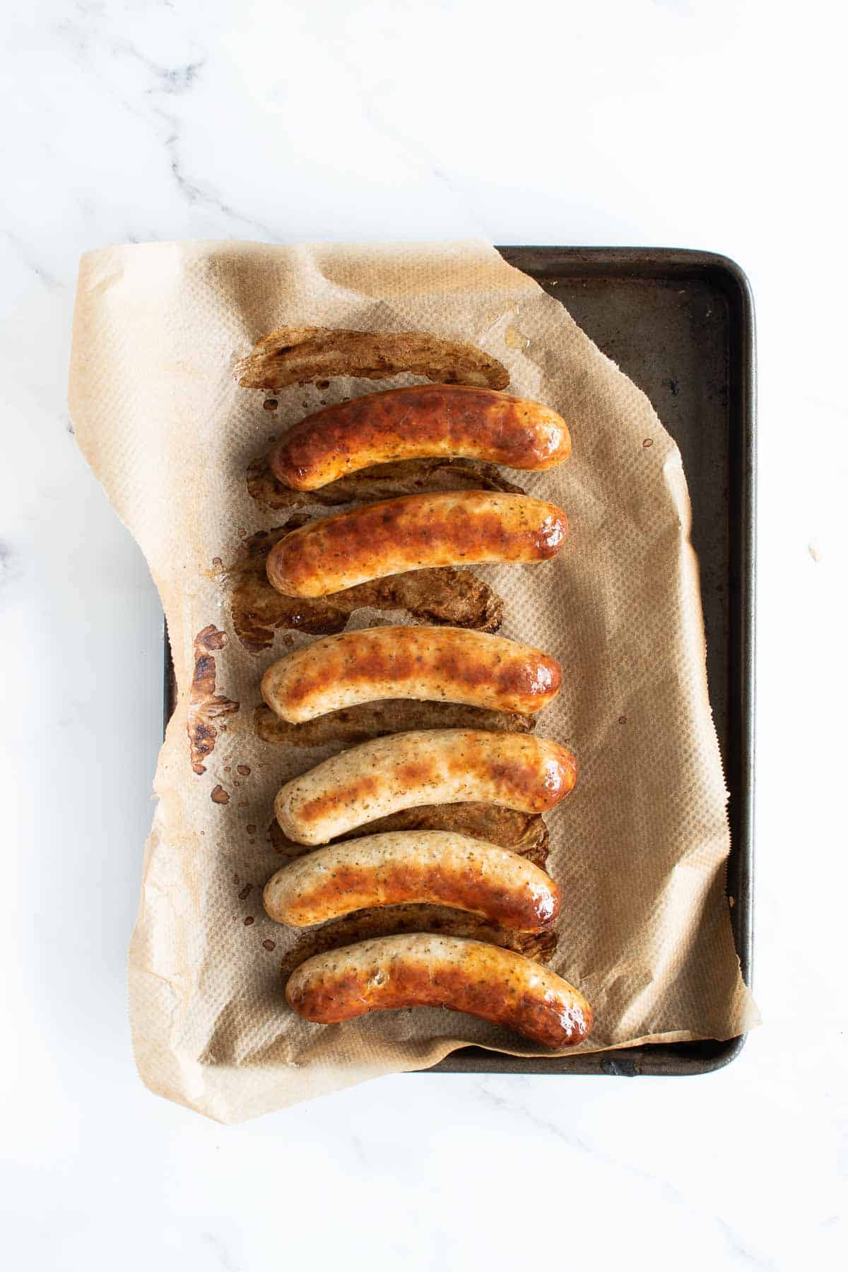 6 cooked bratwurst sausages on a baking sheet.