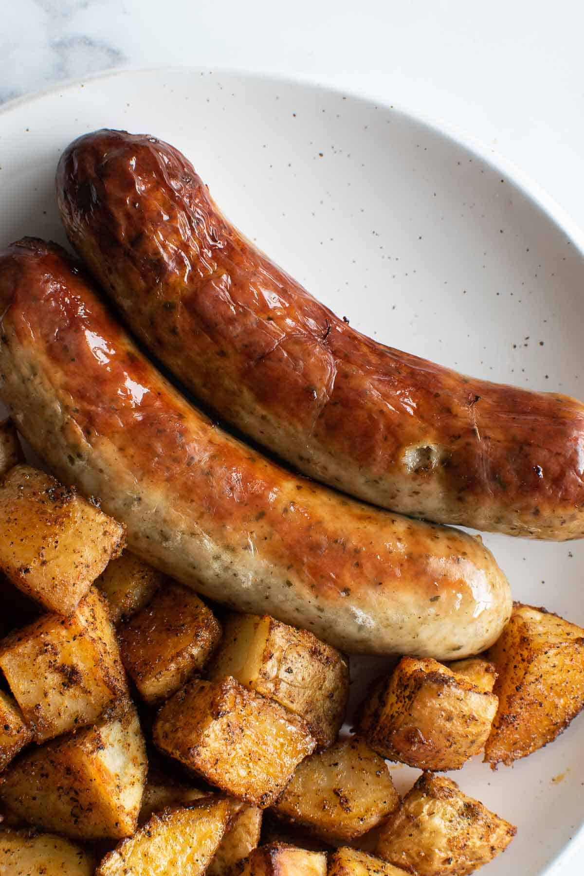 Bratwurst sausages on a plate with roasted potatoes.