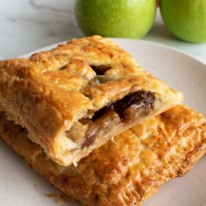 Two puff pastry hand pies with apple filling, with apples in the background.