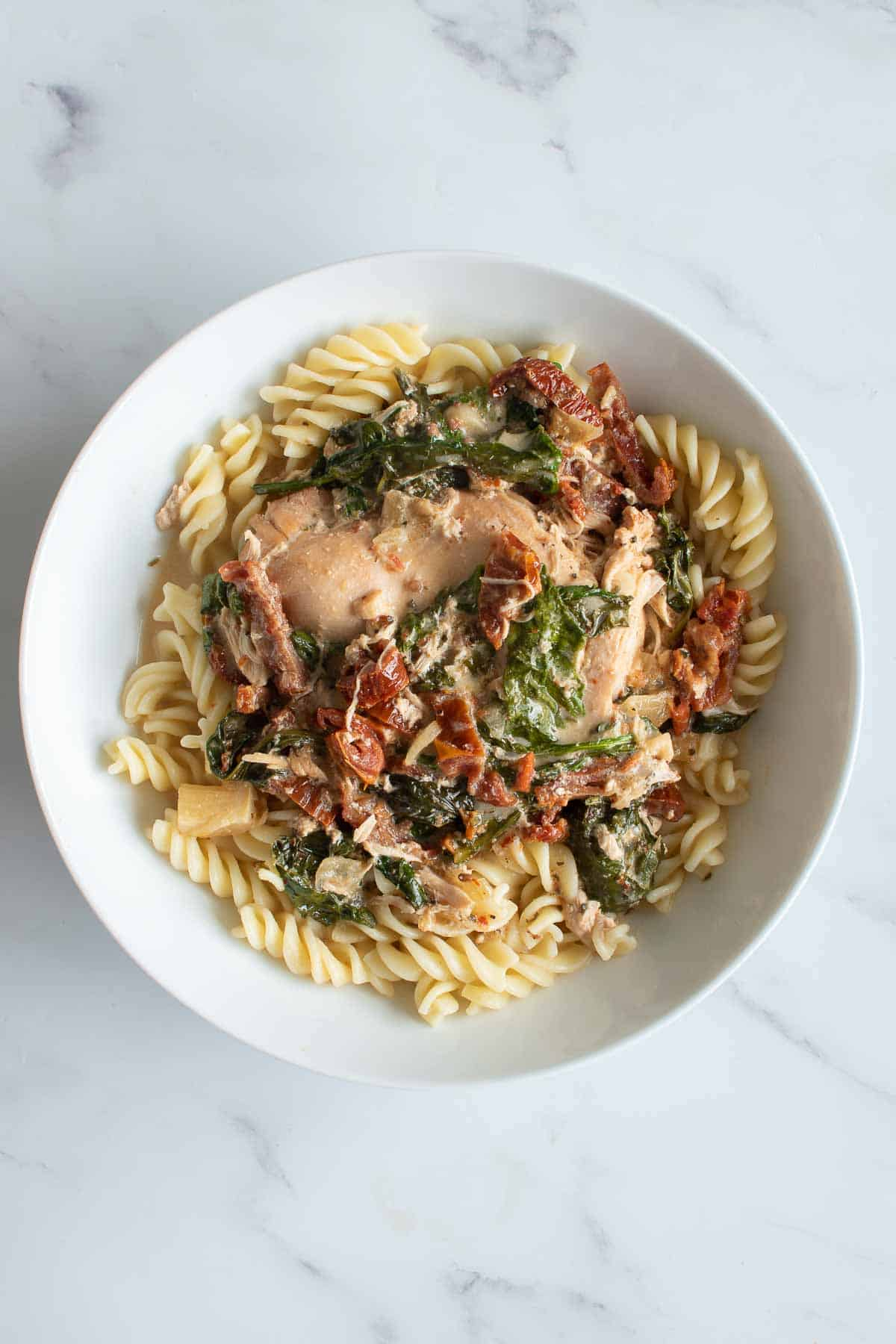 Slow cooked chicken with cream, spinach and sun dried tomatoes over pasta.